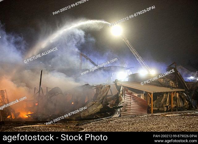 12 February 2020, Baden-Wuerttemberg, Meßstetten: The fire brigade fights the fire in a warehouse for animal feed, which is believed to have caused millions in...