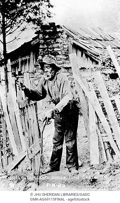 Full length standing portrait of mature African American man wearing a ragged hat, a torn shirt, and no shoes, walking with a cane and opening a gate in front...