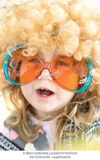 funny portrait of three years old child face disguised as sixties, with great curly blond hair wig on head, with orange and green colorful glasses