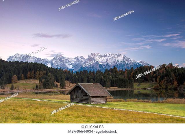 Wooden hut frames the alpine lake surrounded by the Alps Geroldsee Krün Garmisch Partenkirchen Upper Bavaria Germany Europe