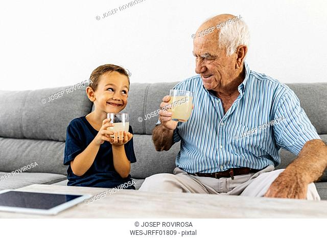 Grandfather and grandson sitting together on couch drinking lemonade