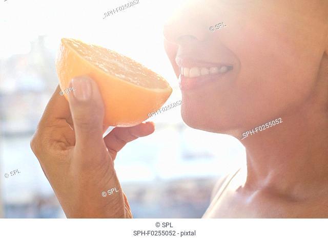 Woman holding half an orange