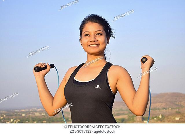 Close-up of Indian Girl with a skipping rope smiling at camera, Pune, Maharashtra