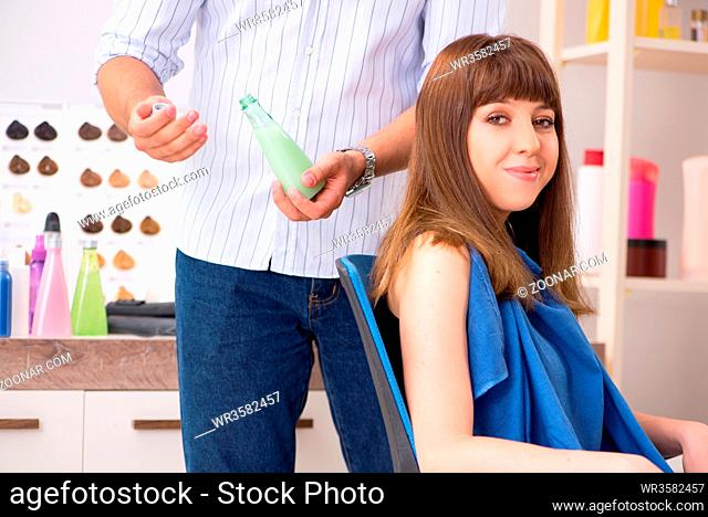 Young woman visiting young handsome barber