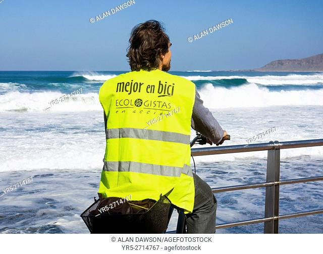 "Cyclist wearing """"Better by bike, Ecologists in action"""" reflective jacket overlooking Las Canteras beach in Las Palmas, Gran Canaria, Canary Islands, Spain"