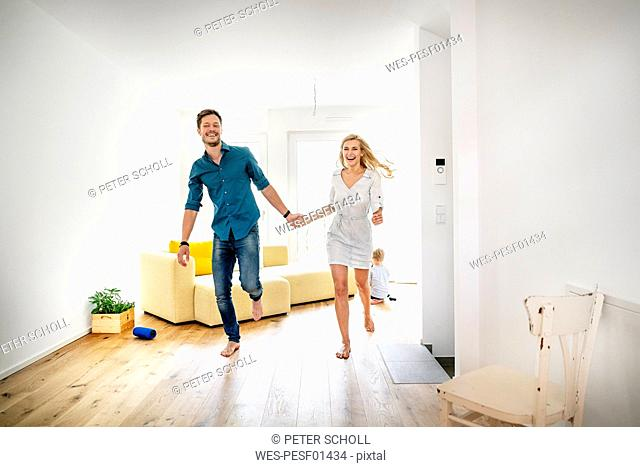 Happy family moving into their new home, parents running hand in hand