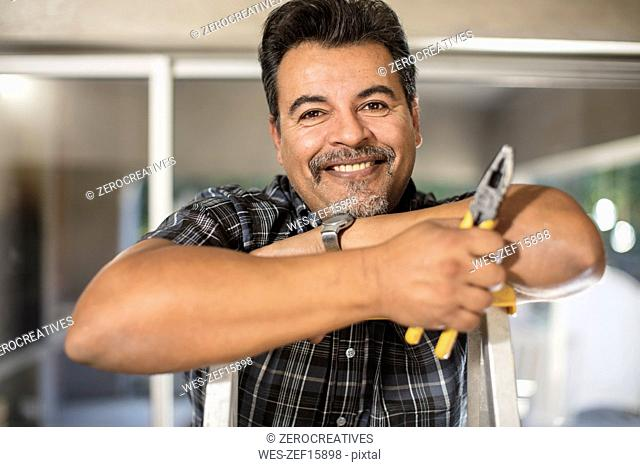 Portrait of smiling man on ladder