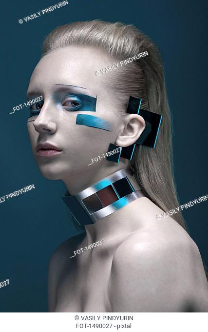 Close-up portrait of confident fashion model against blue background