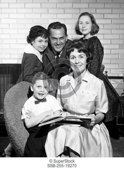 Portrait of a mid adult couple with their three children in a living room