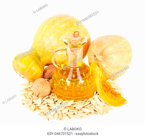 Fresh ripe pumpkin seeds, walnuts and oil decanter isolated on white background