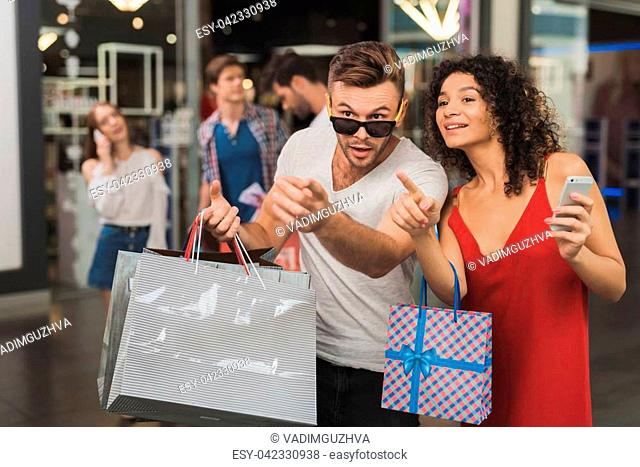 The girl and her boyfriend are shopping at the mall. Sale on a black Friday. A young couple are shopping on a black Friday