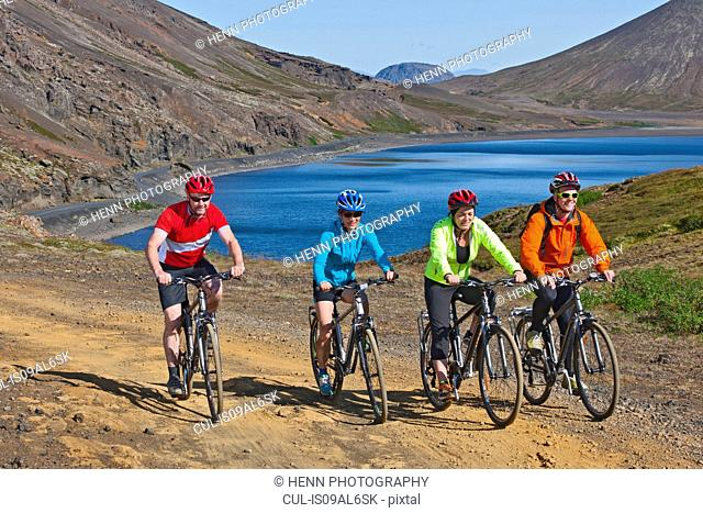 Cyclists cycling up track, Kleifarvatn in background, Reykjanes, South West Iceland