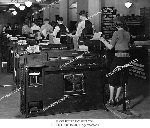 Social Security Administration clerks seated at massive tabulating machines, actually early computers, used to manage the individual records of millions of...