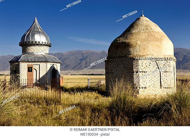Mausoleums in cemetery on steppe of Atyn Emel Park with Koyandy Ak Tau mountain range Kazakhstan