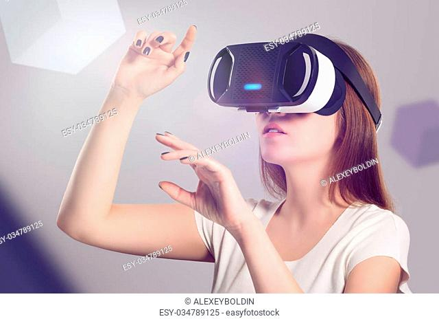 Woman in VR headset looking up and trying to touch objects in virtual reality. VR is a computer technology that simulates a physical presence and allows the...