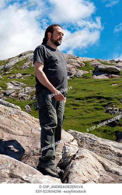 Young handsome caucassian male with dreadlocks enjoying the view on a sunny day trekking in the mounains
