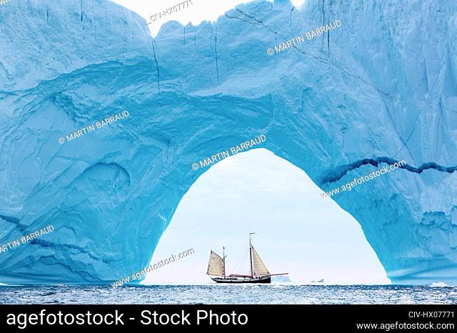 Ship sailing behind majestic iceberg arch Atlantic Ocean Greenland