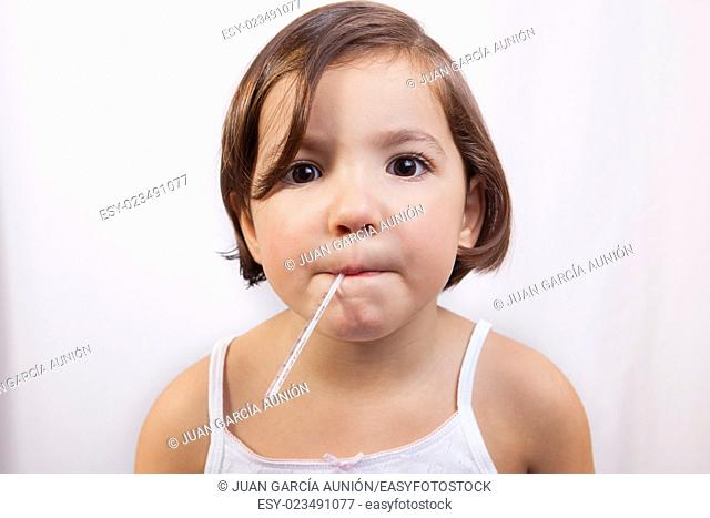 Little girl with a clinical mercury-in-glass thermometer in mouth looking to the camera