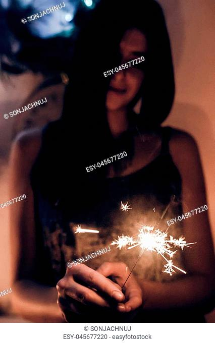 beautiful stylish woman holding burning sparkler bengal light. glowing shining sparkler closeup in female hand in dark. merry christmas concept