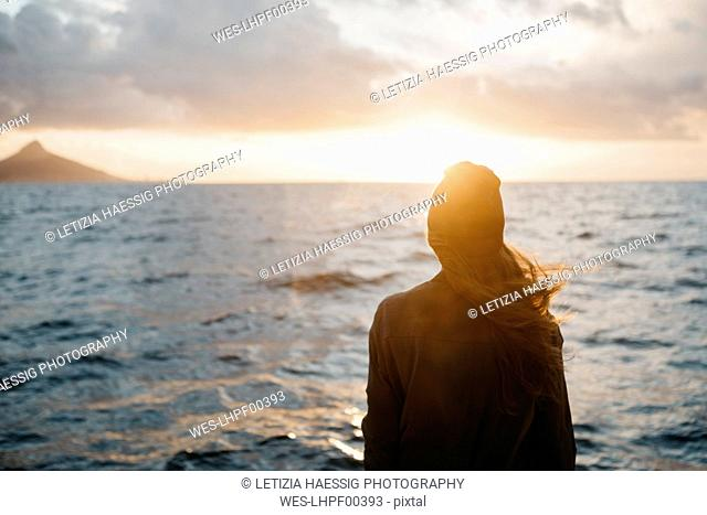 South Africa, young woman with woolly hat during boat trip at sunset