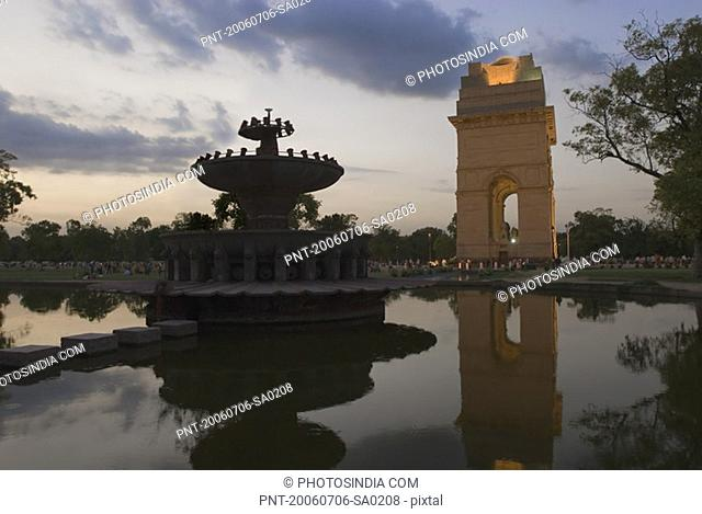 Reflection of a stone gateway in water at dusk, India Gate, New Delhi, India