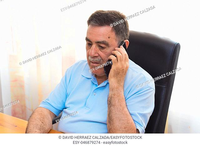 Cheerful Senior Man working on laptop while talking on the phone