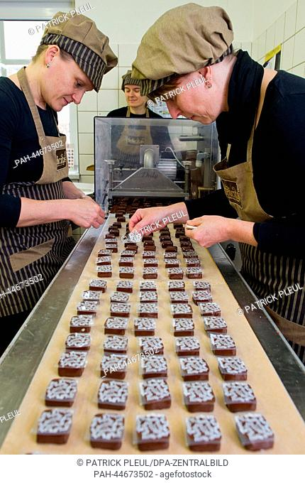 Employees of the Confiserie Felicitas GmbH make chocolates in Hornow, Germany, 02 December 2013. On the same day the first stone was layed for an extened...