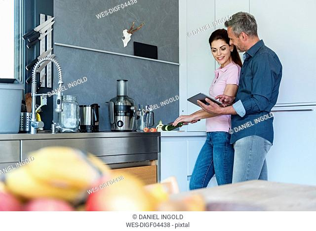 Couple in kitchen at home using a tablet