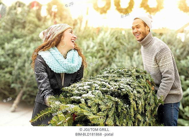 Couple hauling tree at Christmas tree farm
