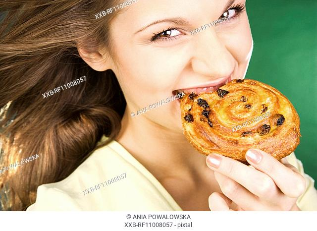 Young woman eating yeast-cake
