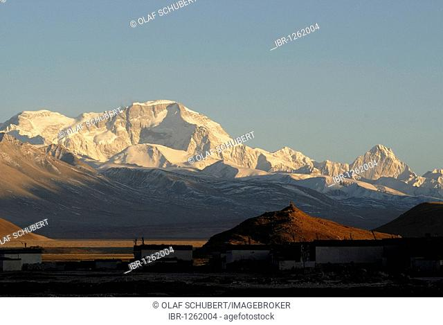 Dusk, sunset in front of the snowy mountains of the Cho Oyo, 8112 m, in the Tingri plateau, with Tibetan buildings of the village of Old Tingri, Tibet, China