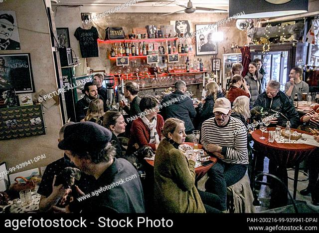 """16 February 2020, Berlin: Visitors of the big dachshund weekend sit with their animals in the guest room of the bar """"""""Posh Teckel Bar"""""""""""