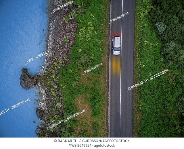 Aerial view of car on Route One by the Lagarfljot river, Fljotsdalur valley, Egilsstadir, Eastern Iceland. This image is shot using a drone