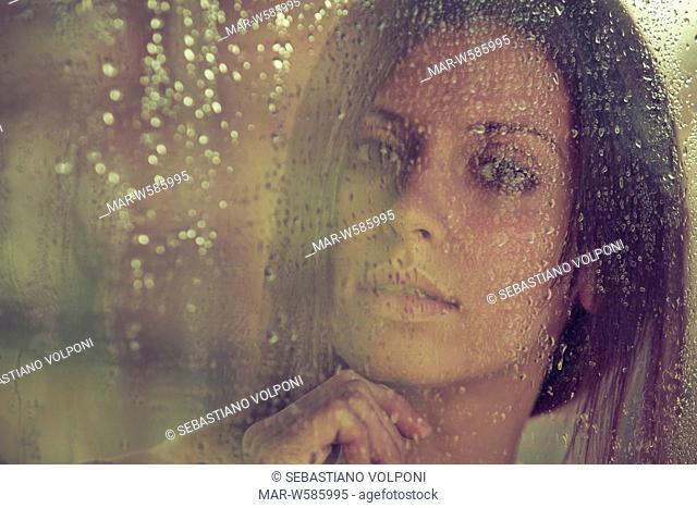 woman behind a wet glass