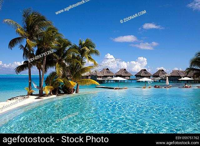 French Polynesia. Over water bungalows, sandy beach with palm trees and pool, Bora Bora