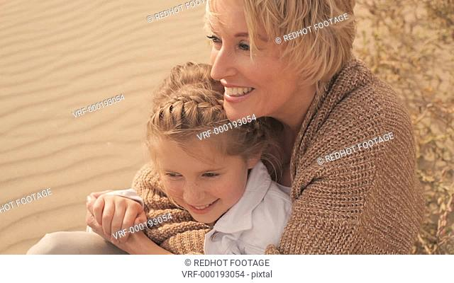 Grandmother and granddaughter sitting and hugging together on windy beach