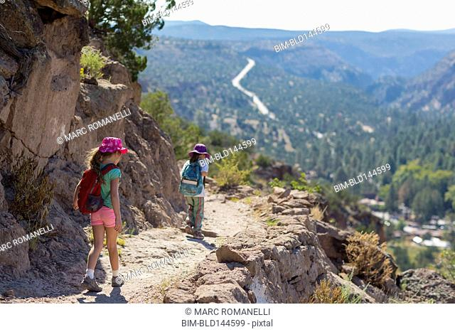 Children hiking together on rocky mountainside
