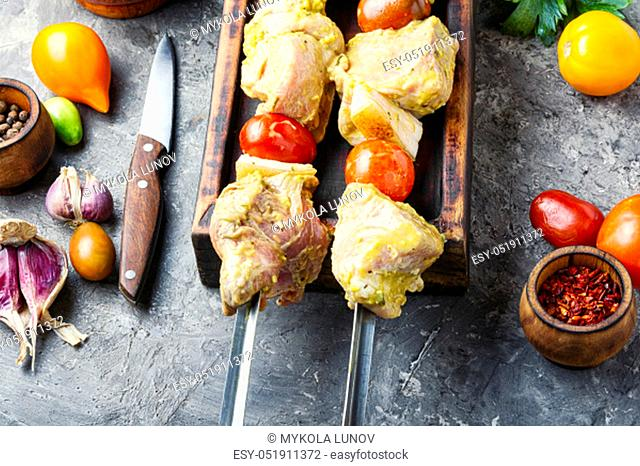 Making kebabs from meat-raw meat on skewers.Marinated BBQ meat