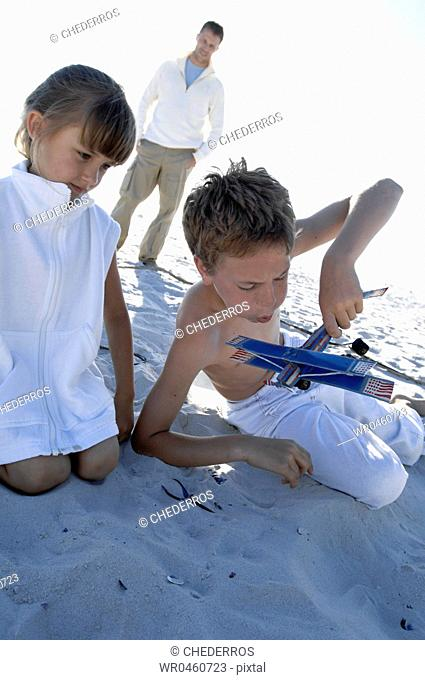 Close-up of a girl and her brother playing with a model airplane with their father standing behind them