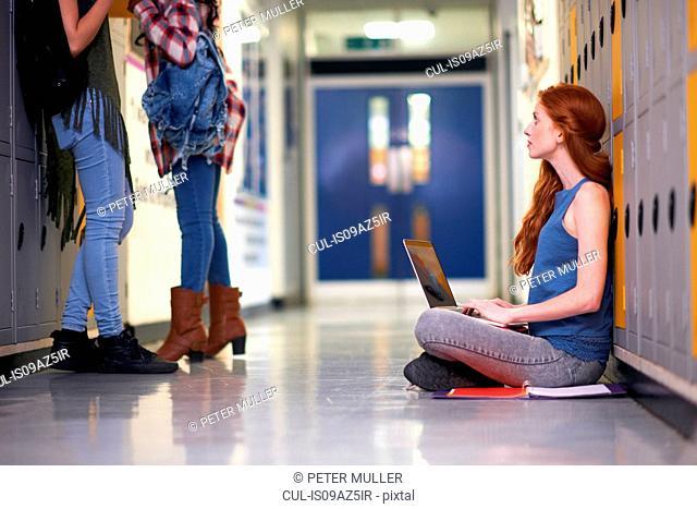 Young female college student sitting on locker room floor looking up whilst typing on laptop