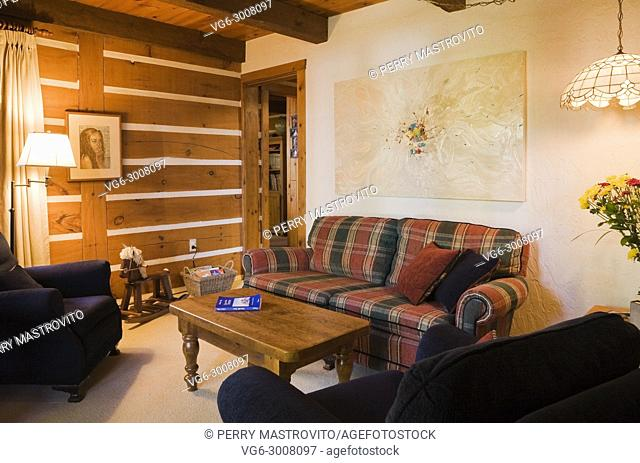 Wooden coffee table, dark blue upholstered sitting chairs and red and green checkered sofa in reading room inside a Canadiana cottage style log home, Quebec