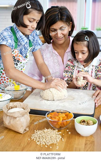 Mother baking with girls in kitchen