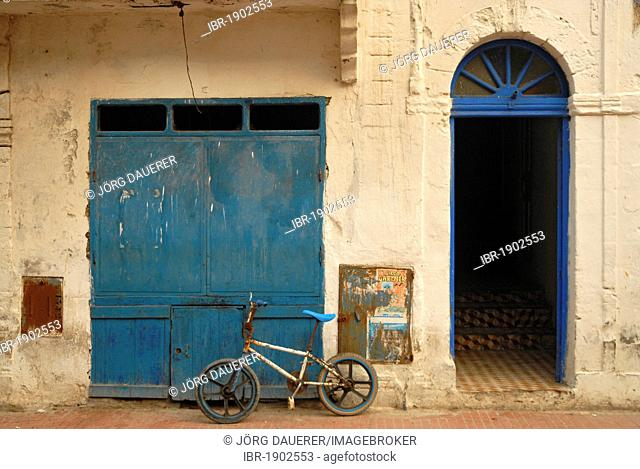 Bicycle in front of a facade with a blue gate in Essaouira, Morocco, Africa