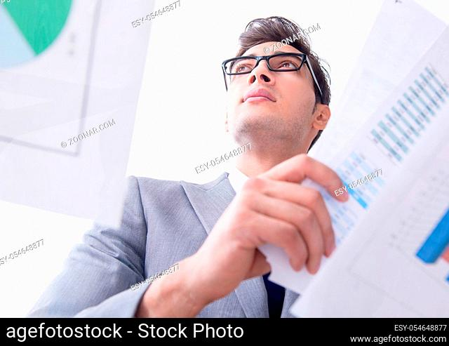 The businessman looking at financial charts and graphs
