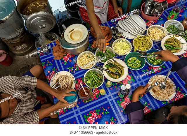 A street kitchen with noodle dishes at a market in Bangkok, Thailand