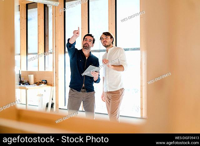 Two businessmen with tablet talking at the window in wooden open-plan office