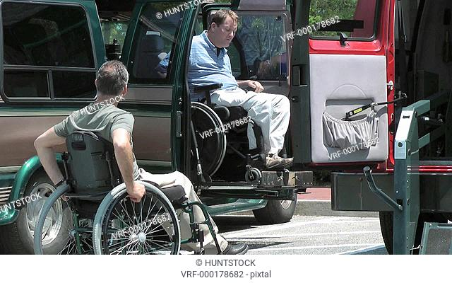 Two men with spinal cord injuries in wheelchairs, one entering accessible van