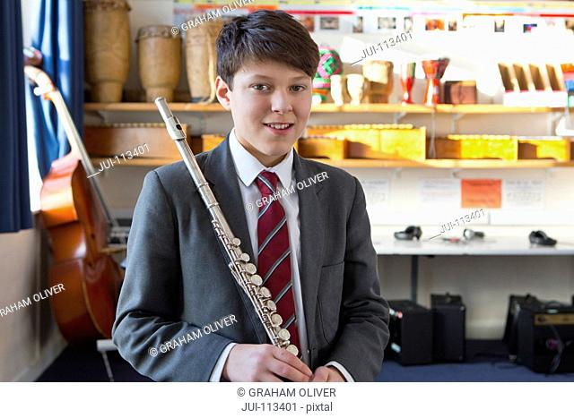 Portrait smiling middle school student holding flute in music classroom