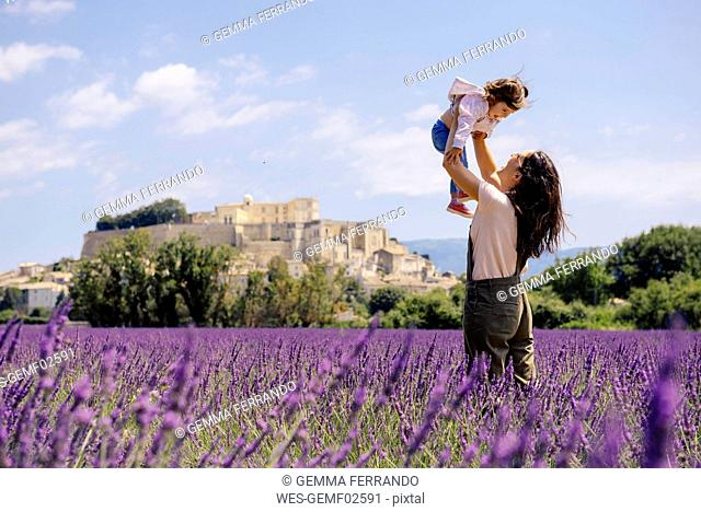 France, Grignan, mother and little daughter having fun together in lavender field