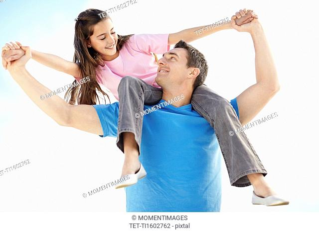 Father carrying daughter 10-11 on back